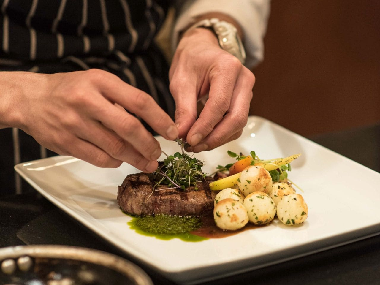 Chef plating steak and potatoes