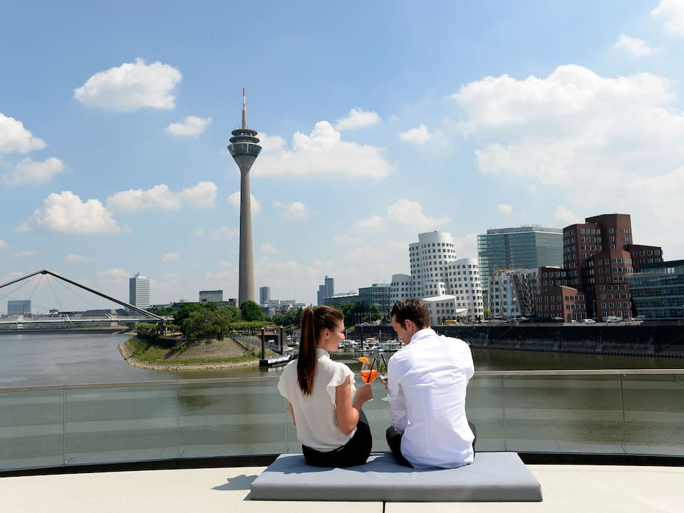 Couple sitting on Dusseldorf riverfront