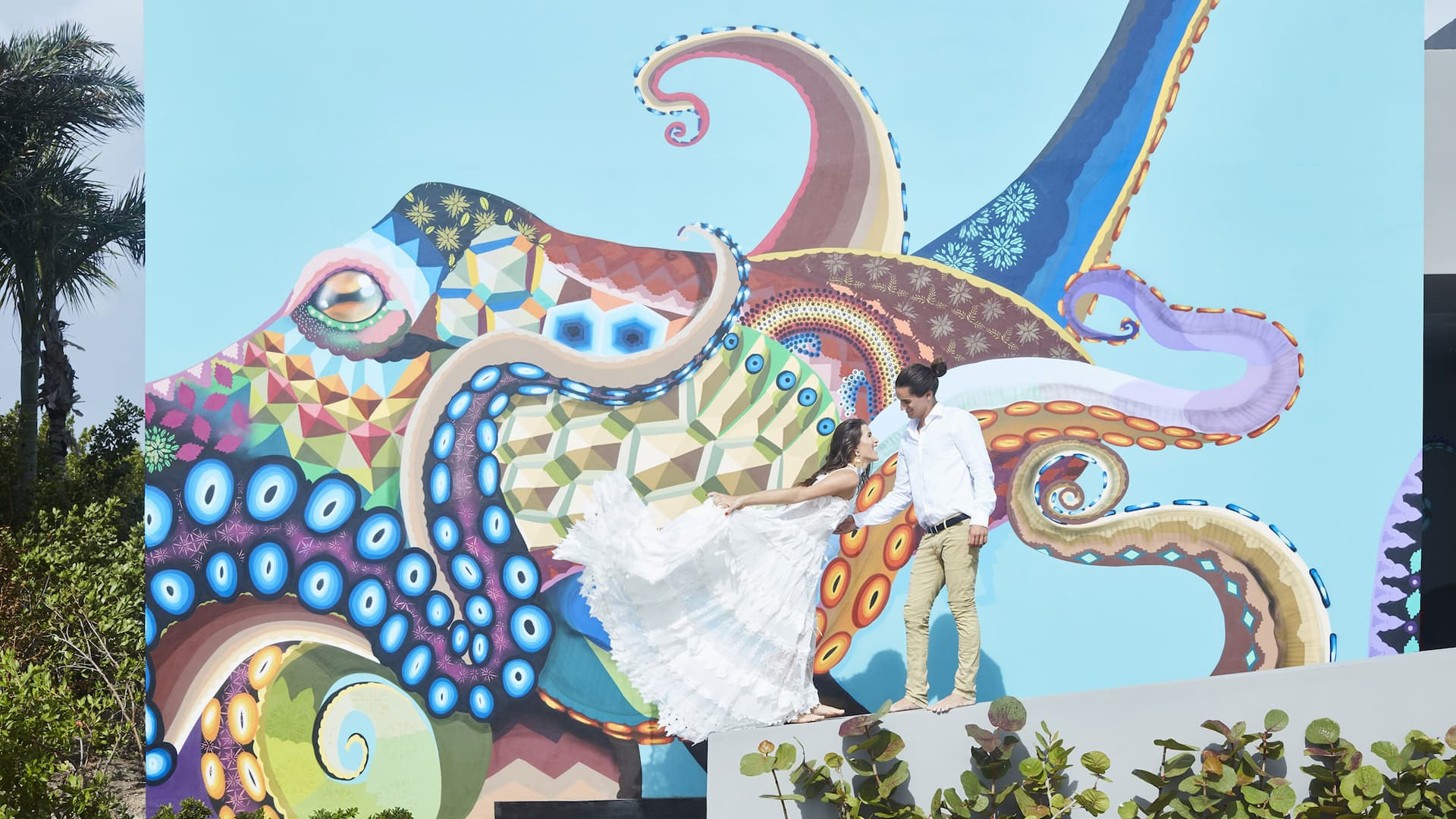 Couple posing for a casual wedding photo in front of a mural in Riviera Maya