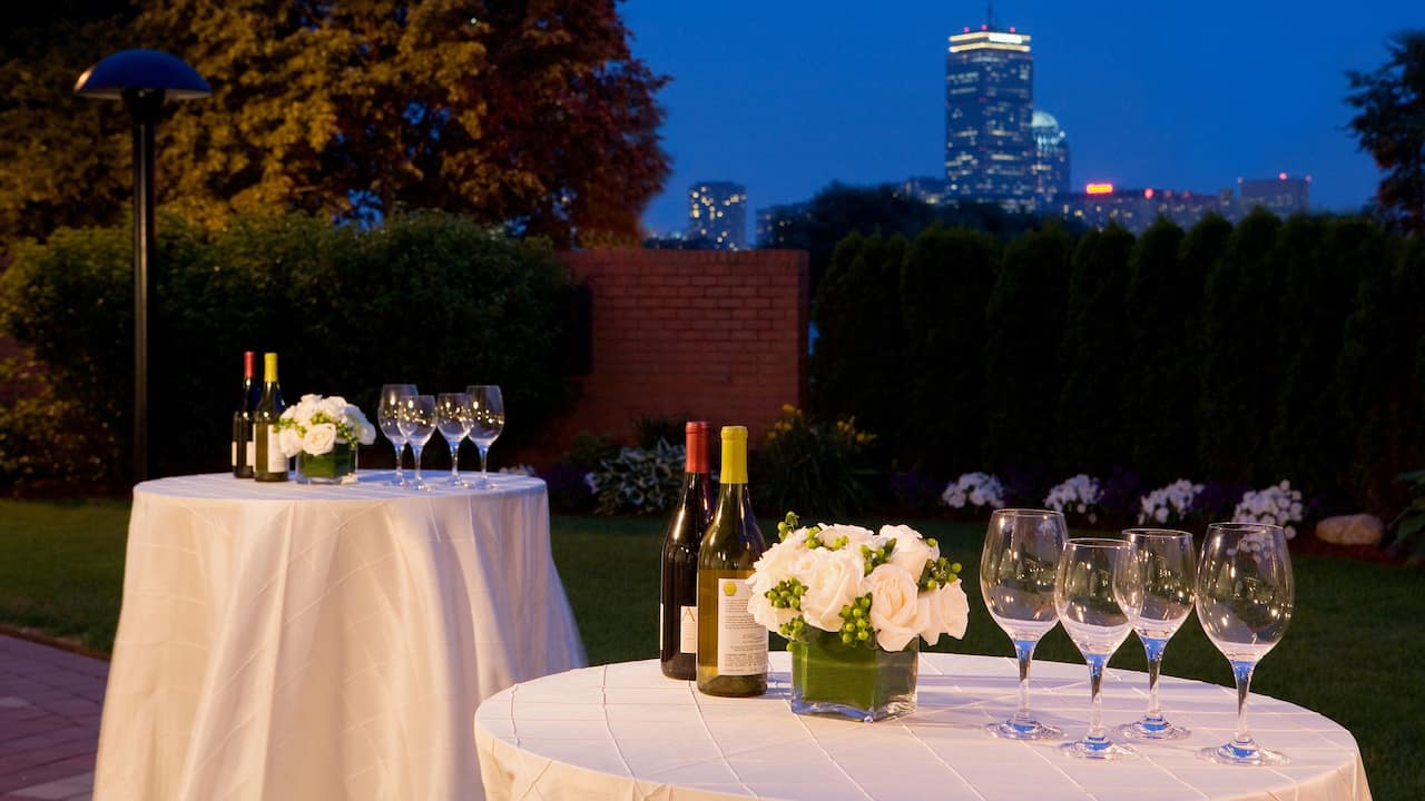 Tables with white table arrangements and wine set outside with a view of Boston