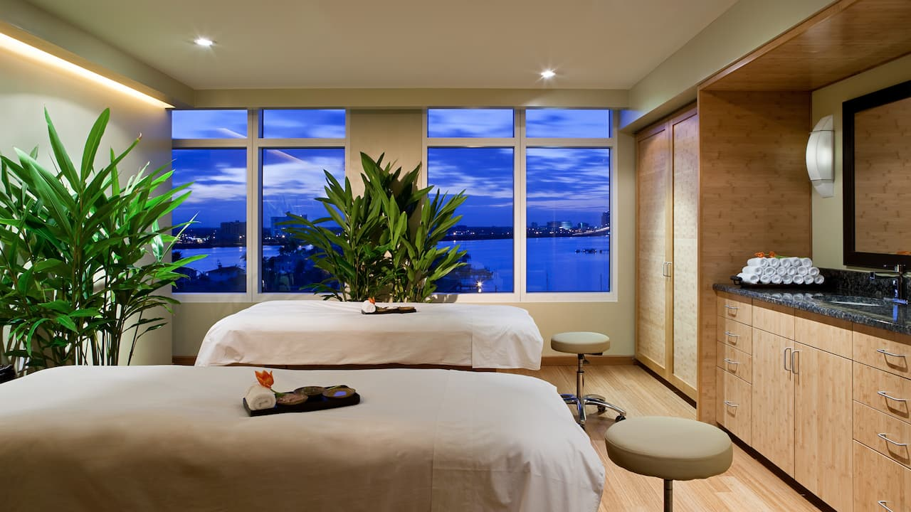 Two massage tables in spa room with night time ocean view