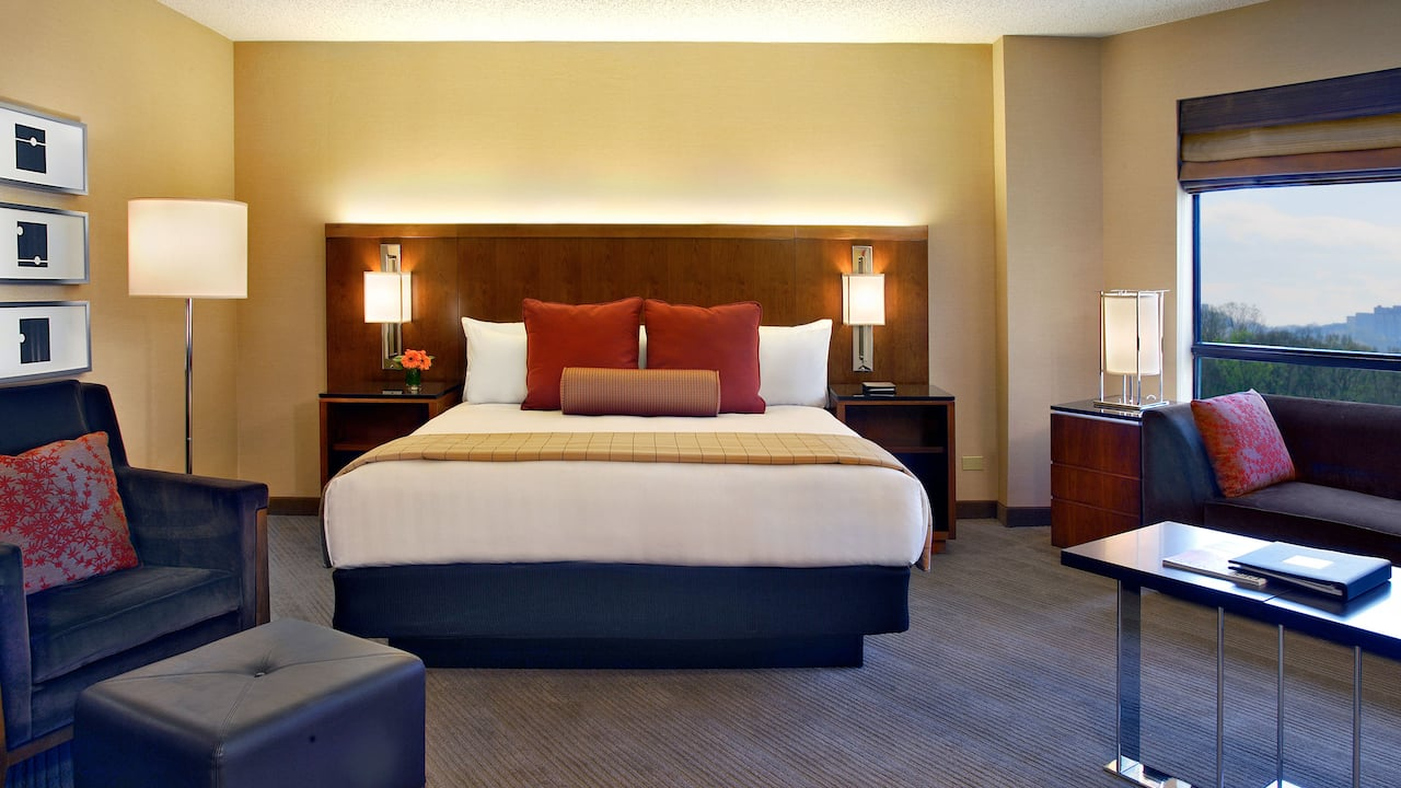 King-sized bed by large window in hotel room