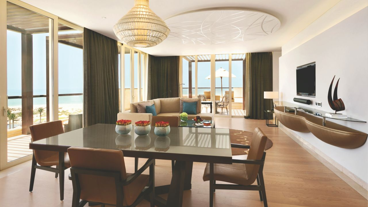 Terrace Suite living room, dining table with balcony overlooking beach