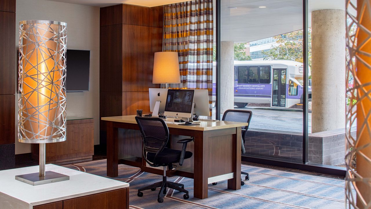 Desk with computer and lamp in hotel business center