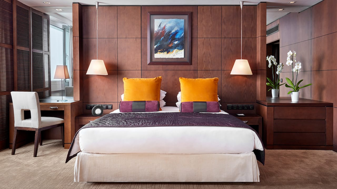 King-sized bed between hanging two lamps in hotel suite