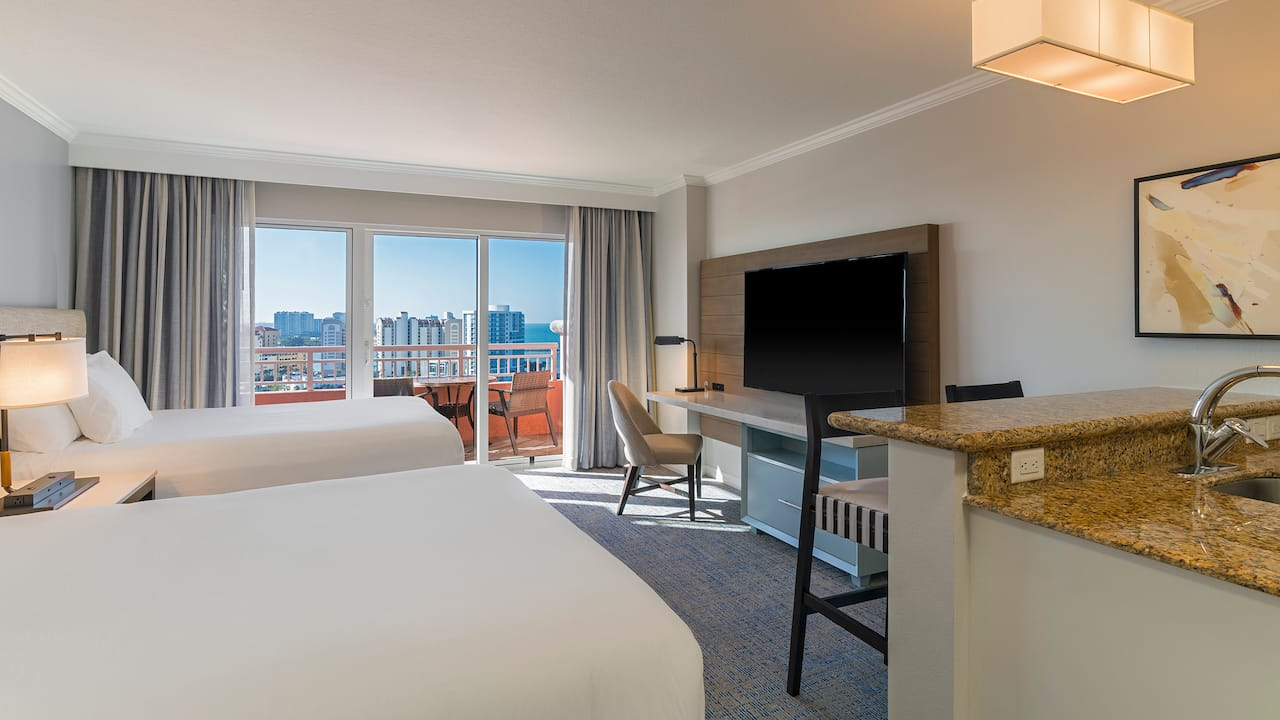 Two queen-sized beds by large window in hotel room