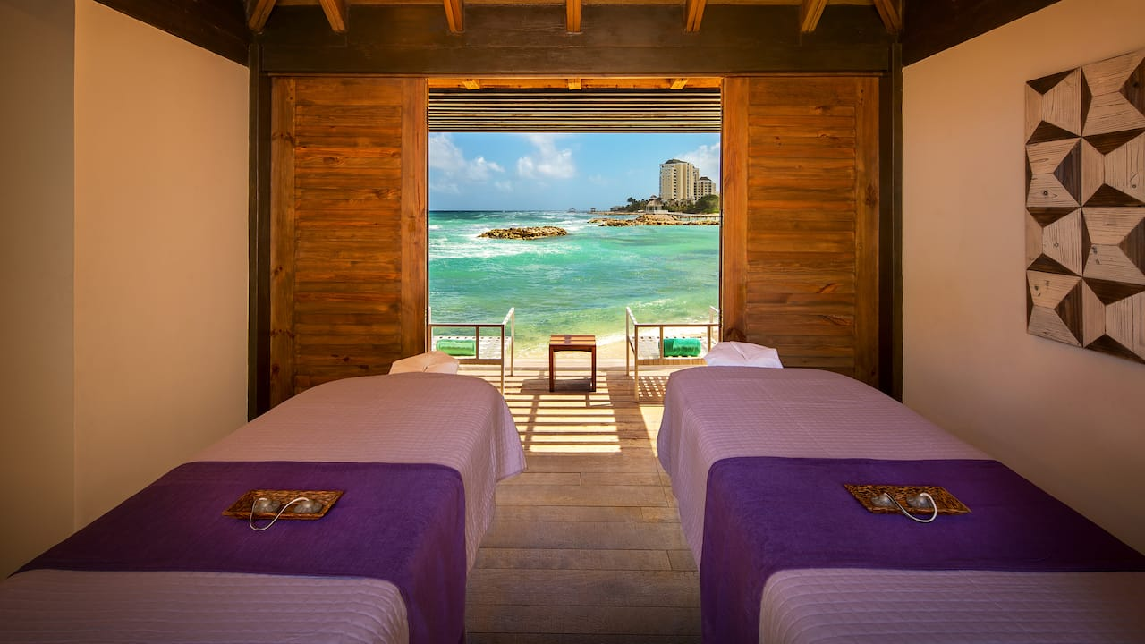 Man and woman receiving massages on separate tables in open beachfront room at Zen Spa