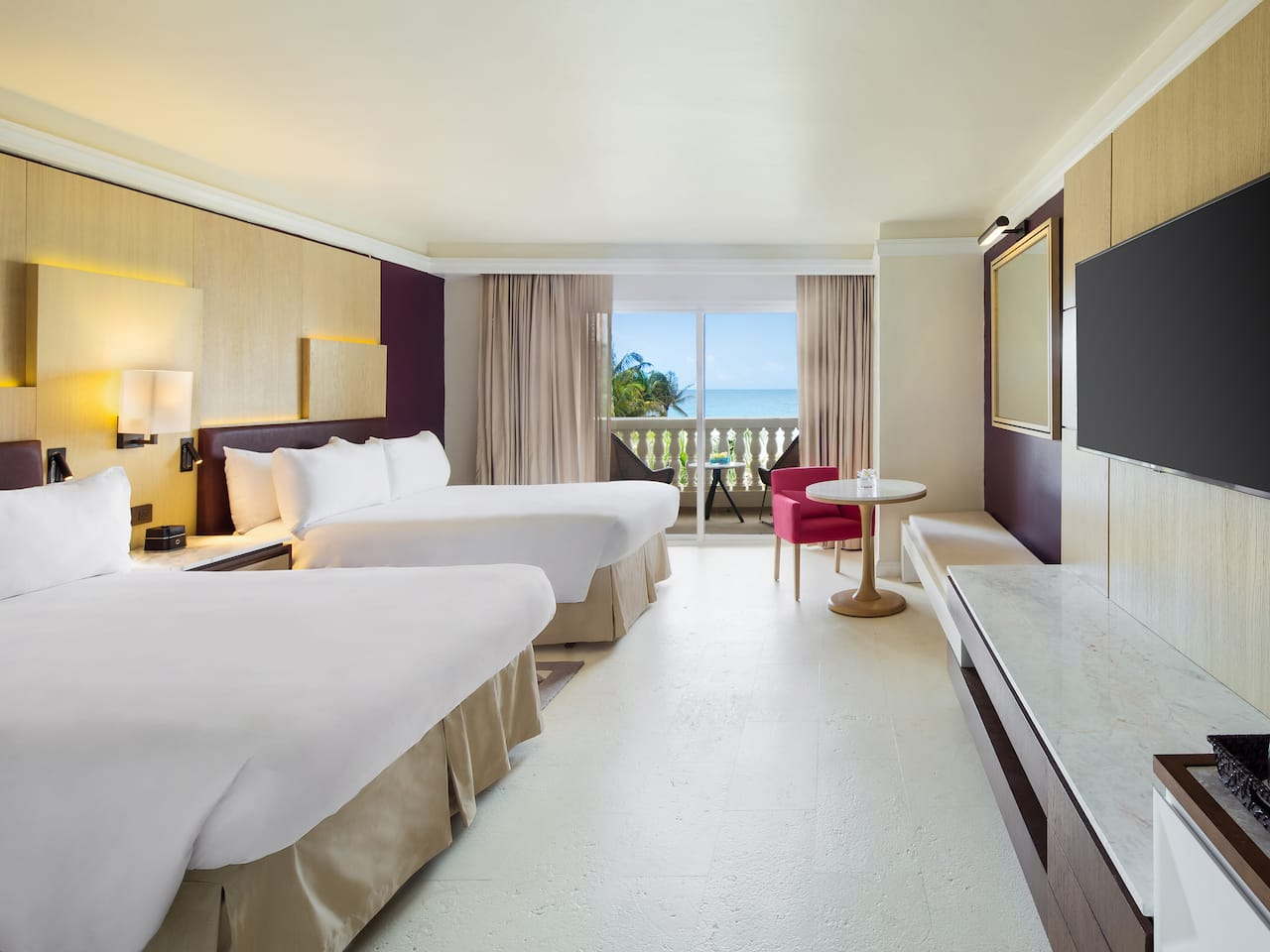 King sized bed by large patio window in resort guestroom