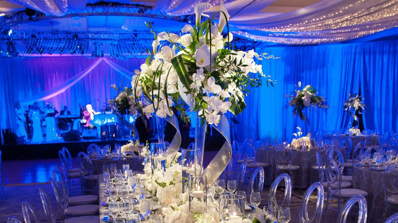 Wedding table set up with place settings, large flower bouquets, and blue backdrop