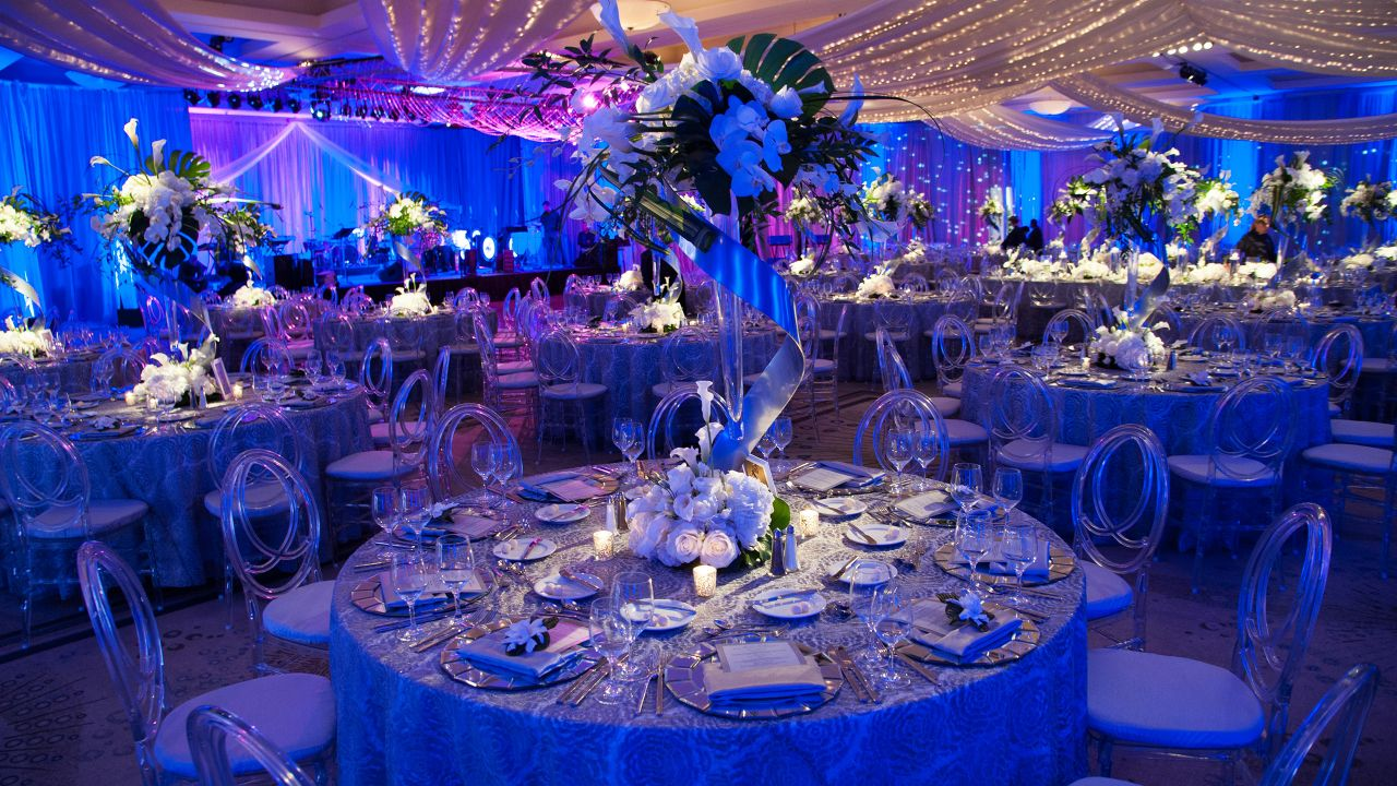 Wedding table set up with place setting, flower bouquets, and blue backdrop