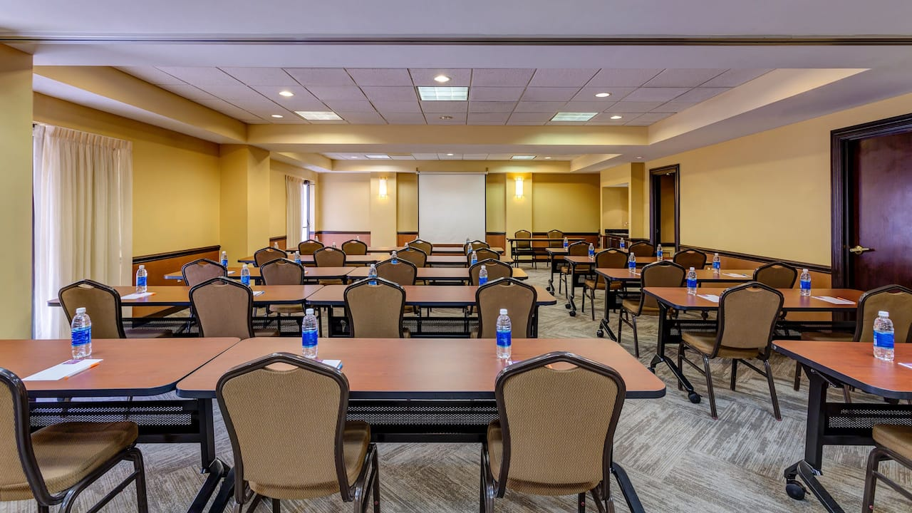 Rows of tables and chairs in hotel meeting room
