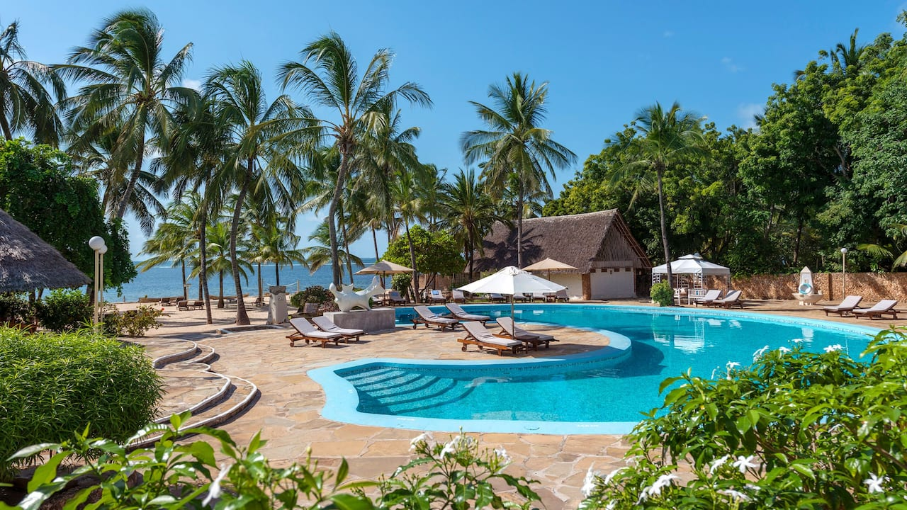 Diamonds Dream of Africa Outdoor pool surrounded by lush gardens and palm trees