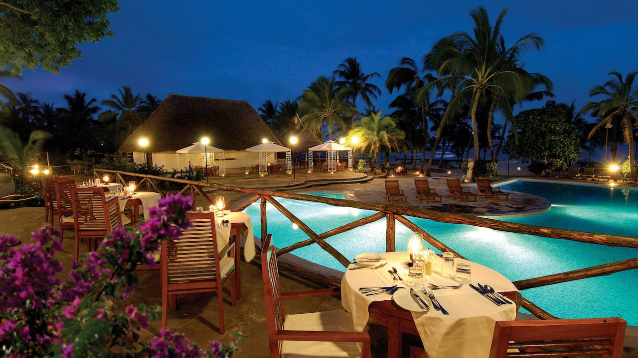 Diamonds Dream of Africa Restaurant terrace looking out at resort pool at night
