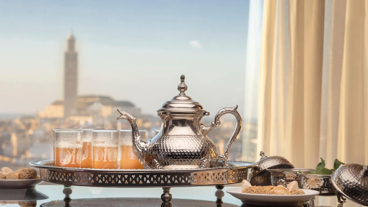 Ornate teapot with two cups on tray by window