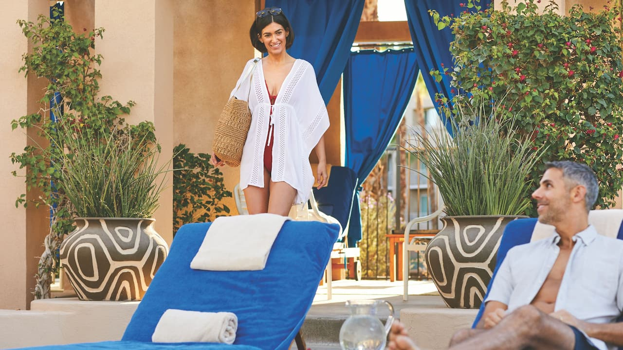 An adult couple relaxing at a reserved cabana near the Oasis adult pool offered at Hyatt Regency Indian Wells Resort & Spa