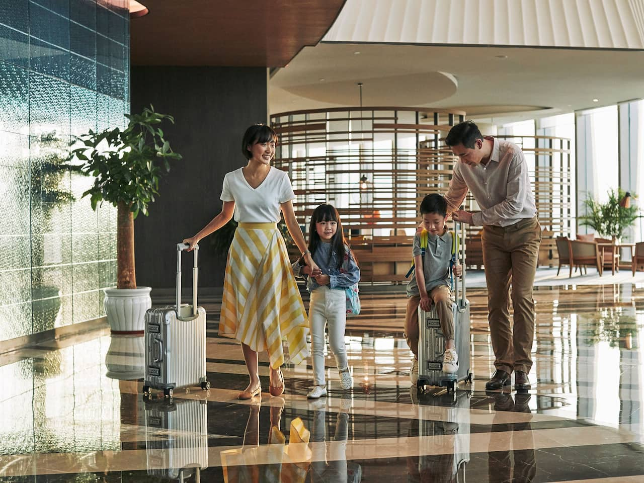 WOH_P345_Leisure_Travelers_Family_Lobby_Rolling_Suitcases