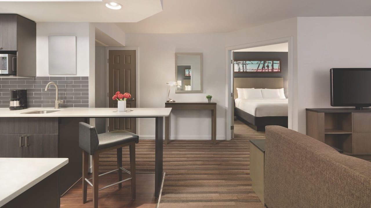 Two-bedroom suite facing doorway to bedroom with kitchen counter at Hyatt House Boston / Burlington