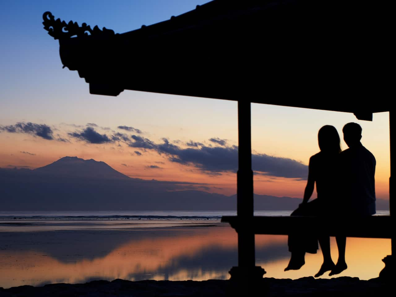 Couple is enjoying sunrise at Sanur Beach with Mount Agung view