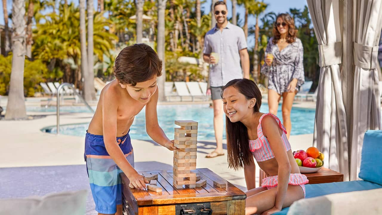 Two kids playing Jenga by the pool at a Mission Bay hotel near Seaworld