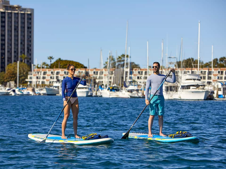 A man and a woman paddleboarding on the water near a San Diego hotel