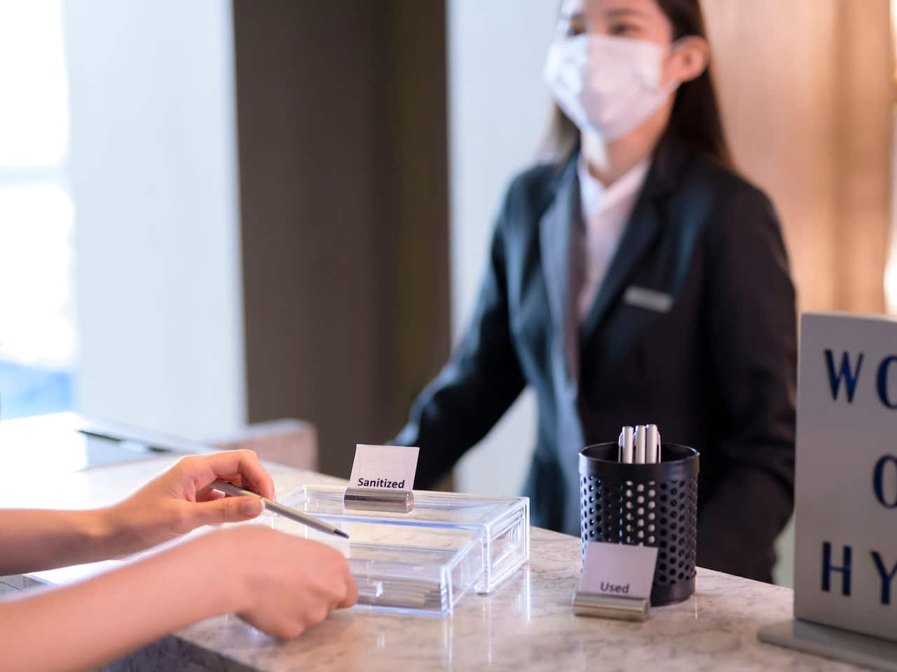 Sanitizing Front Desk Pen with Staff