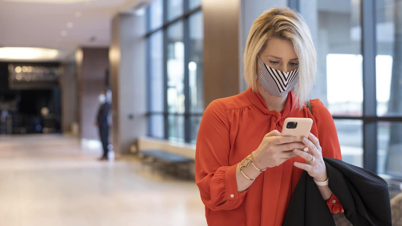 Woman Traveler in Hotel Lobby with Face Mask Checking Phone