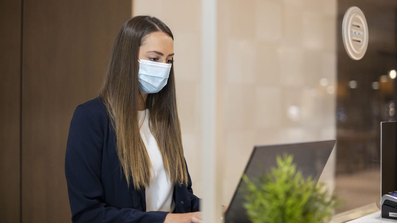 Front Desk Agent with Face Mask Working Behind Safety Glass