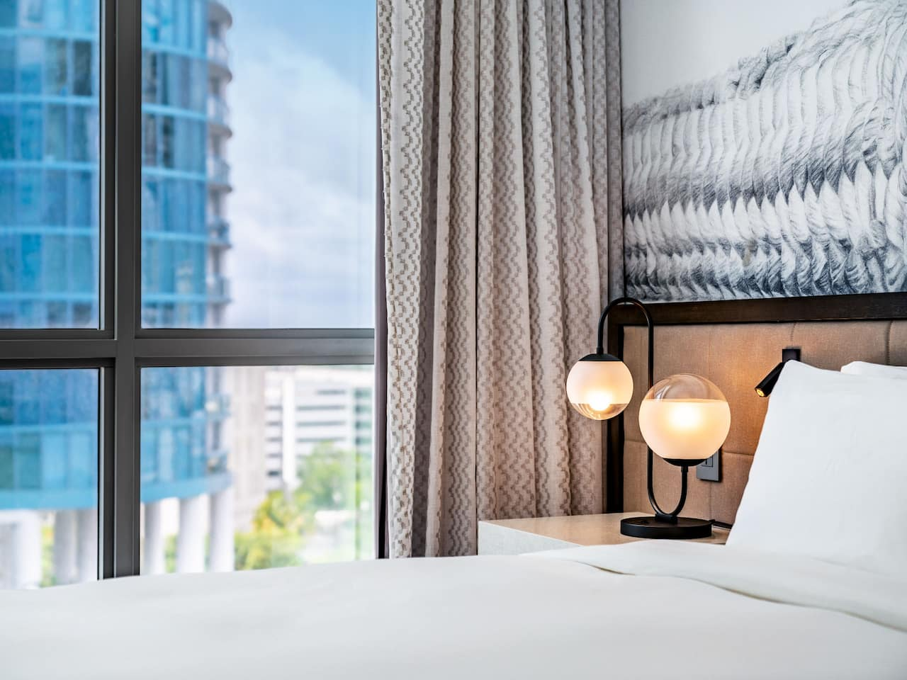 Close Up Of The Hotel Bed Next to a Window Overlooking Downtown Fort Lauderdale on Las Olas Blvd