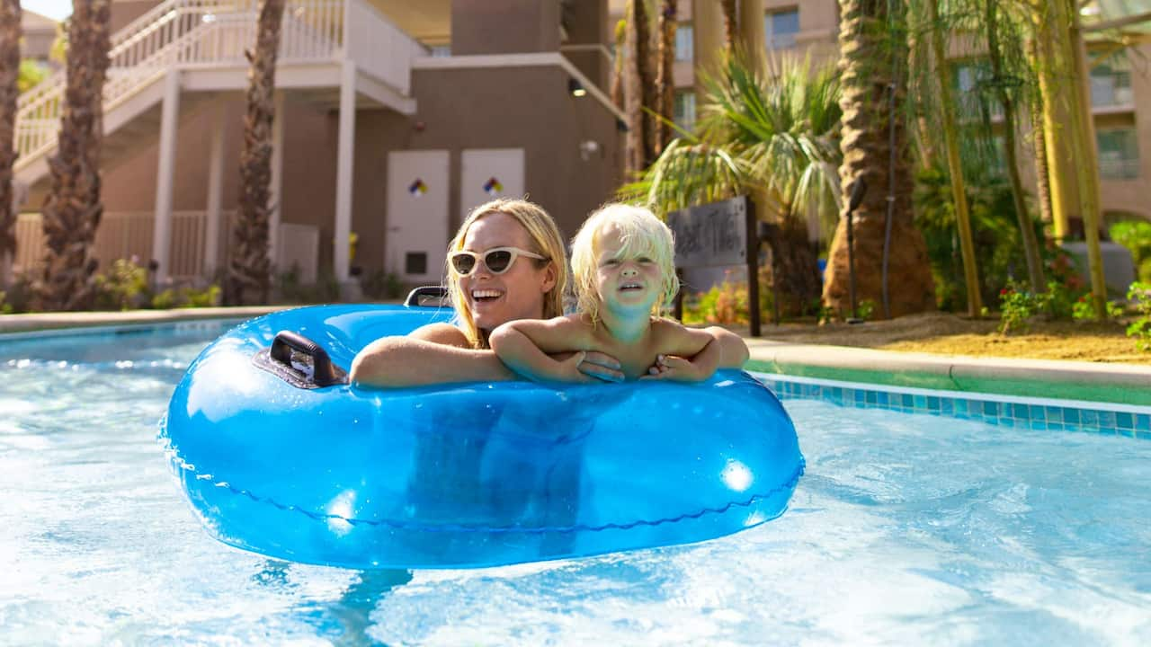 A mother and her child floating on an inner tube in a family-friendly lazy river