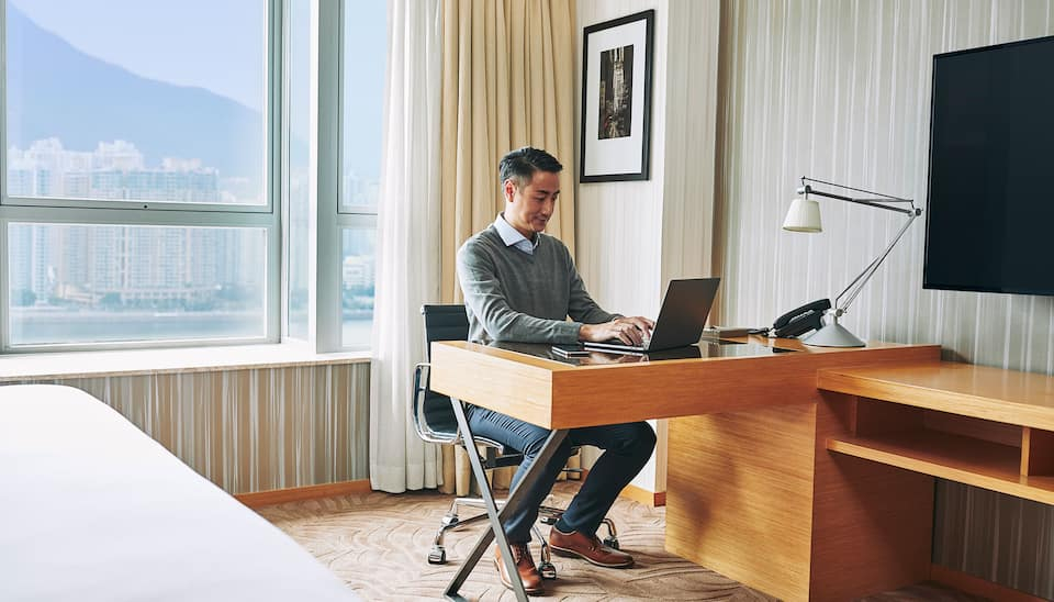 Man working at desk in hotel room