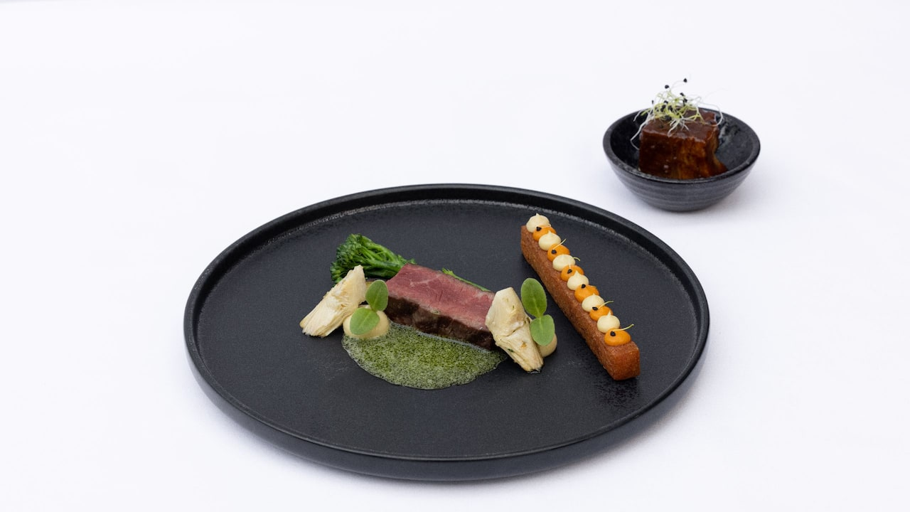 Beef sirloin and green sauce on a black plate