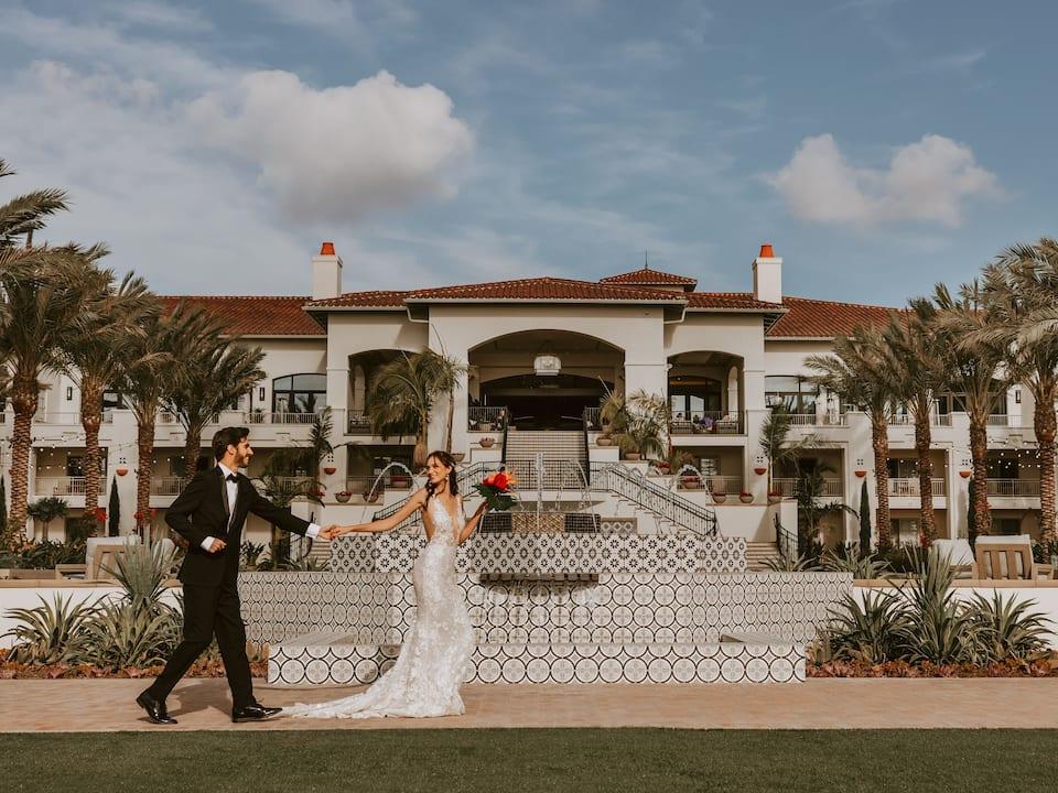 Newlyweds walking through a wedding venue in Carlsbad, CA