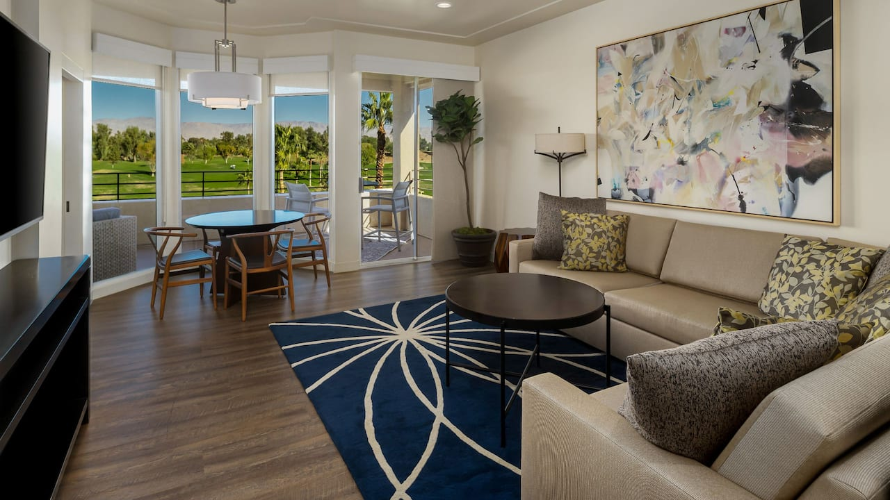 A luxurious penthouse suite with a balcony view overlooking a golf course and mountain views at Indian Wells