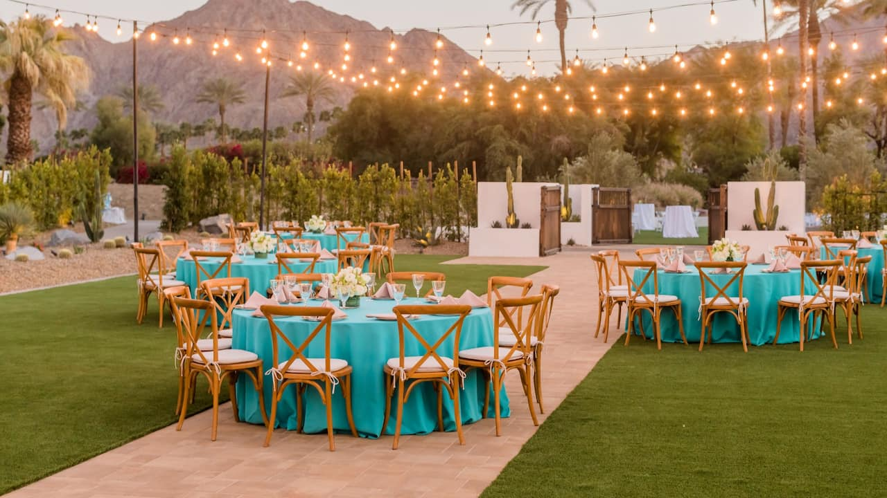 An outdoor wedding reception with green draped tables in Palm Springs